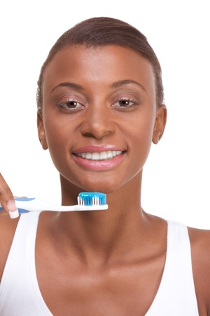 Portrait of black woman holding toothbrush with blue toothpaste and smiling
