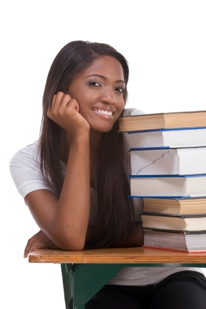 High school or college ethnic African-American female student sitting by the desk with lot of books in class or library