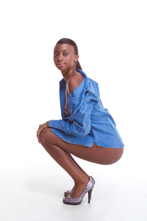 Squatting Young topless female fashion model of African-American ethnicity wearing just jeans jacket and otherwise naked Archivio Fotografico