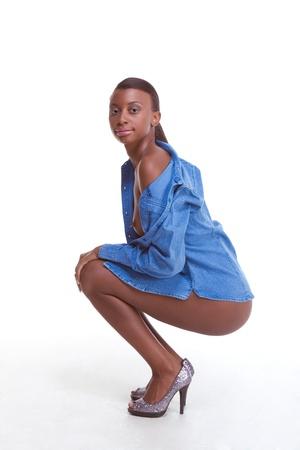 Squatting junge topless weiblichen Mode Model des afro-amerikanischer Herkunft tragen nur Jeansjacke und ansonsten nackt