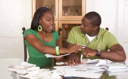 pagando: Joven pareja afroamericano negro sentado por tabla de vidrio y tratando de trabajar a trav�s de la pila de proyectos de ley, frustrados por importe de gastos durante la recesi�n de las crisis econ�micas veces esperando para que plan de est�mulo trabajar o esperando el dinero del rescate