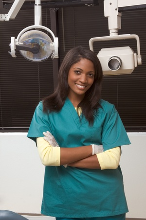 Young smiling black ethnic Afro-American female dentist assistant standing in dental office by chair Archivio Fotografico