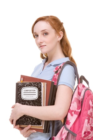 Friendly Caucasian High school girl student standing with backpack and holding books, notebooks and composition book photo