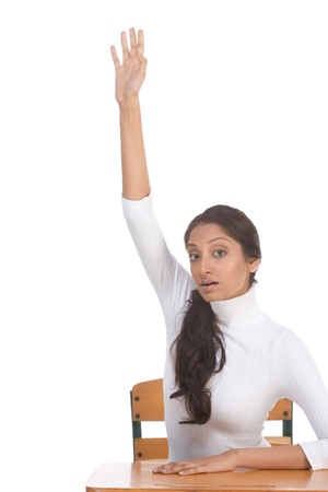 High school or college female student sitting by the desk raising her arm signaling that she know and is ready to answer photo