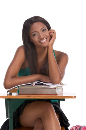 african american ethnicity: High school or college ethnic African-American female student sitting by the desk with books and copybook in class