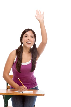 at her desk: High school or college female student sitting by the desk raising her arm signaling that she know and is ready to answer