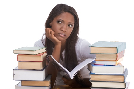 High school or college ethnic African-American female student sitting by the desk with lot of books in class or library and doing homework Stock Photo - 9040722