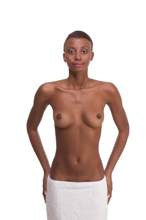 Young ethnic topless black female with slicked back hair wrapped in white bath towel around her hips after sauna photo
