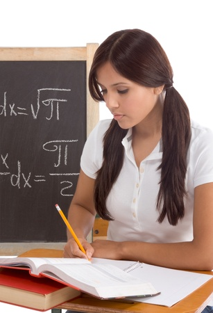 Latina High school or college female student sitting by the desk at math class. Blackboard with advanced mathematical formals is visible in background