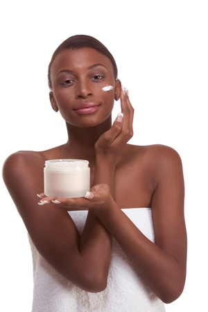Skincare - Young ethnic African-American woman with slicked back hair wrapped in white bath towel applying cream moisturizer on her face after sauna