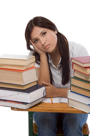 bored High school or college Latina female student sitting by the desk with pile of books in front of her Banque d'images