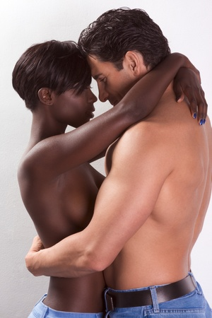 Loving affectionate nude heterosexual couple in sensual kiss and hug. Mid adult Caucasian men in late 30s and young black African-American woman in 20s Stock Photo - 9165219