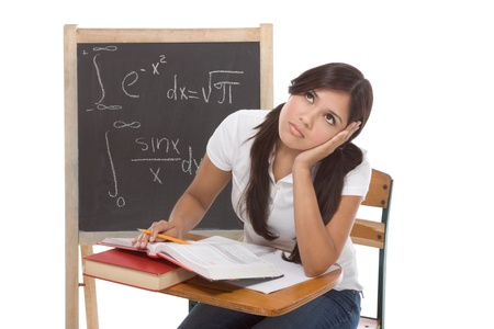 Stressed High school or college Latina female student sitting by the desk at math class. Blackboard with complicated advanced mathematical formals is visible in background photo