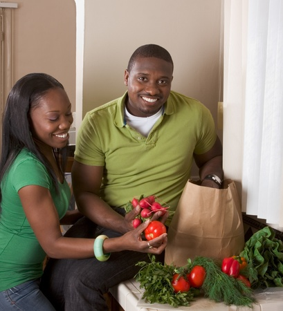 Young ethnic couple on kitchen sorting groceries Standard-Bild