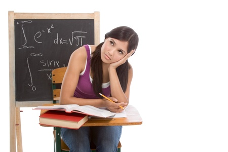 tired High school or college Latina female student sitting by the desk at math class. Blackboard with complicated advanced mathematical formals is visible in background photo