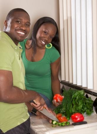 Young Black African American paar voorbereiding groente salade op aanrecht in de keuken