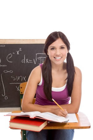 High school or college female student sitting by the desk at math class. Blackboard with advanced mathematical formals is visible in background