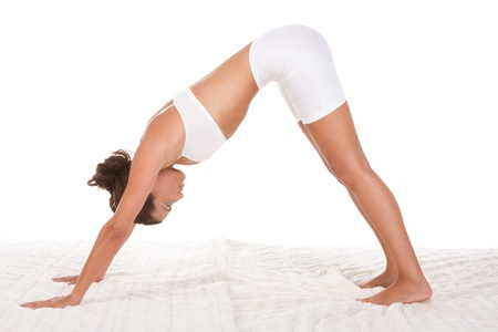 yoga pose Downward facing dog - female in sport clothes performing exercise photo