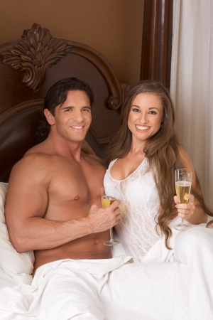 Young sexy heterosexual couple celebrating with wine in bed Stock Photo - 9498536