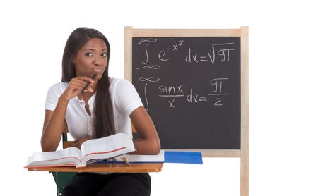 Stressed High school or college ethnic African-American female student sitting by the desk at math class. Blackboard with complicated advanced mathematical formals is visible in background photo