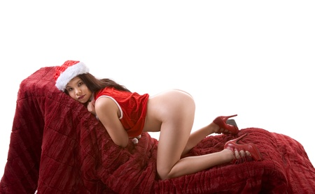 Sensual woman stripper in Mrs Santa Claus costume and Santa hat on red couch undressing