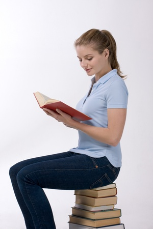 Young Caucasian female college student in jeans sitting on stack of books and reading open book from library