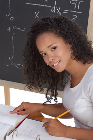 High school or college African-American black female student sitting by the desk at math class. Blackboard with advanced mathematical formals is visible in background Stock Photo - 9681514