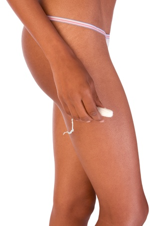 Close up of black ethnic woman hips and her hand holding white vaginal cotton tampon photo