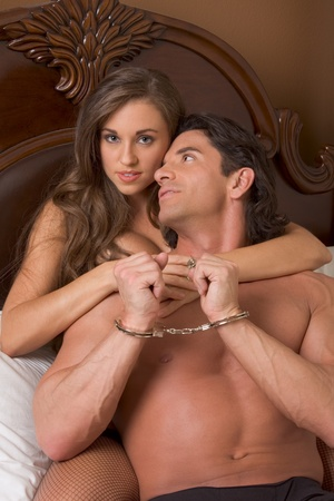 Sexy Caucasian couple in love sexual games, man in handcuffs Stock Photo - 9773460