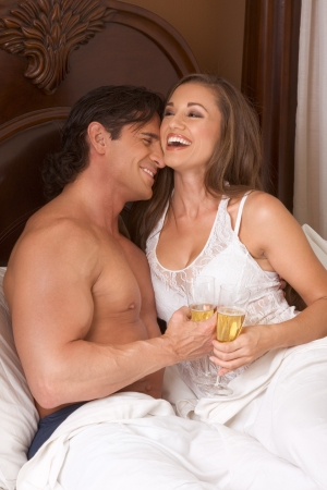 Young sexy heterosexual couple celebrating with wine in bed Stock Photo - 9897415