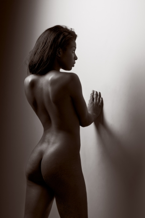 Nude young dark skinned sensuality charged Latina female with perfectly shaped ass standing leaning on wall with her back turned to viewer (toned) Stock Photo - 9897410