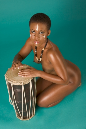 Portrait of African American woman wearing original tribal themed face-paint and necklace playing Conga drum photo