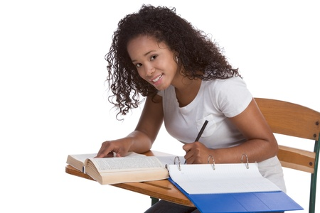 ethnic black woman high school student sitting by school desk doing homework photo