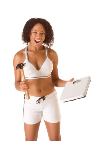 Ethnic woman in sporty outfit hits weight scales by hammer Stock Photo - 10119461