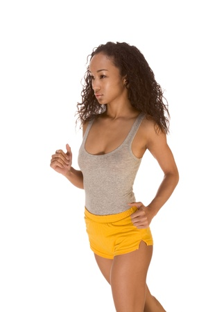 Young biracial dark skinned female of Chinese, African-American, German and Middle Eastern origin in tank top and shorts jogging photo