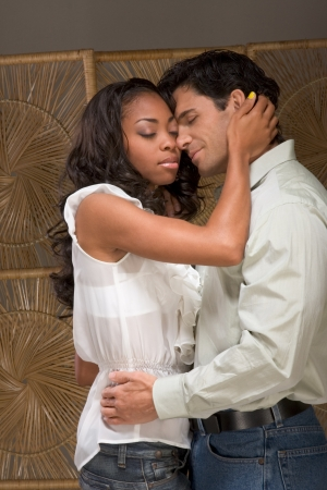 Loving affectionate heterosexual couple in affectionate sensual kiss. Mid adult Caucasian men in late 30s and young black African-American woman in 20s