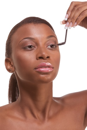 Young female beauty ethnic fashion model of African-American ethnicity holding mascara makeup brush photo