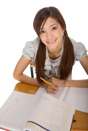 Asian student girl sitting by the desk and studying huge math book, preparing to test