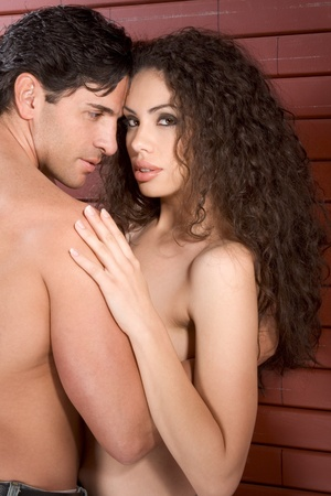 Loving affectionate nude heterosexual couple in affectionate sensual kiss. Mid adult Caucasian men in late 30s and young Latina woman in early 20s Stock Photo - 10277674