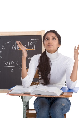 square root: High school or college ethnic Indian female student sitting by the desk at math class. Blackboard with advanced mathematical formals is visible in background