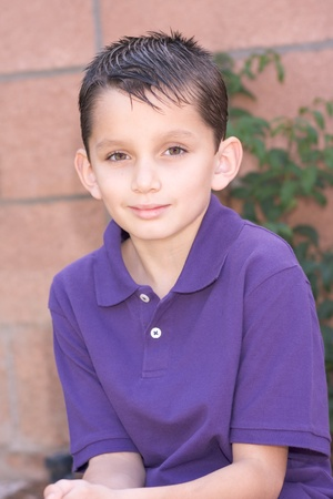 short sleeve: Headshot of elementary age kid in short sleeve polo shirt. Multi-ethnic of Caucasian and Hispanic (Mexican) mix