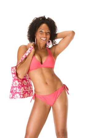 Dark skinned black female in pink swimsuit holding beach bag photo