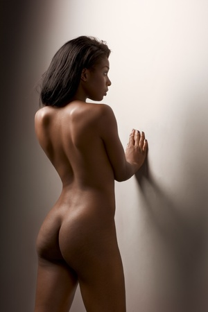 Nude young dark skinned sensuality charged Latina female with perfectly shaped ass standing leaning on wall with her back turned to viewer Stock Photo - 10313713