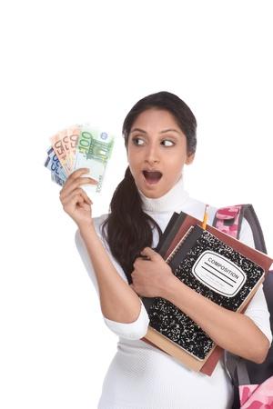 brunnet: Estudiante universitario indio �tnicos con composiciones port�tiles, cuadernos y suspensiones de mochila pila de billetes de euro Foto de archivo