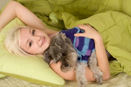 russian ethnicity: Caucasian blond young woman lying down on bed and holding dog of Schnauzer breed Stock Photo