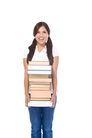Young Hispanic female college student in jeans holding huge pile of educational books from library