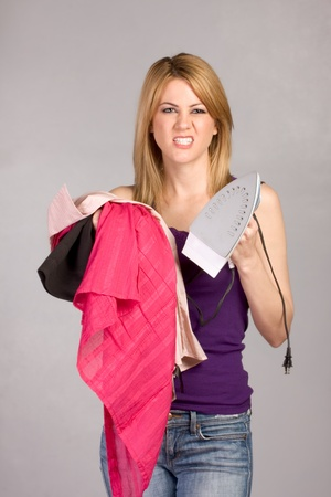 clenching: Young blond woman hunted by hose chores holding stack of wrinkled garments and electric cord iron in her hands