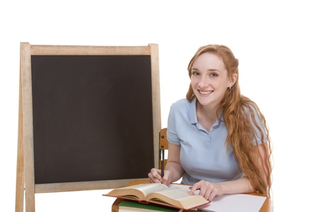school desk: High school or college Caucasian redhead woman student sitting by the desk. Blank blackboard with copyspace is visible in background
