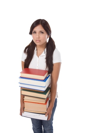 Young Hispanic female college student in jeans holding huge pile of educational books from library photo