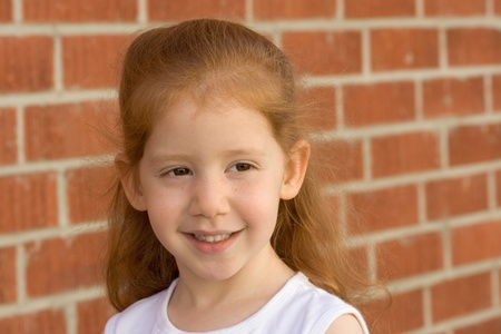 Portrait of Young smiling redhead kid girl by brick wall photo